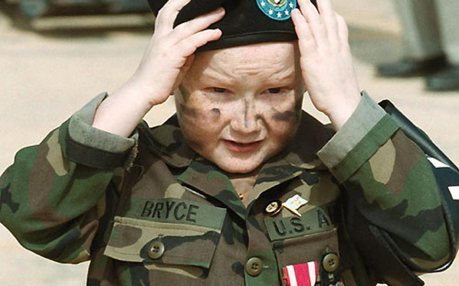 Justin Bryce, 10, adjusts his beret given to him by the Army. The Make-A-Wish Foundation helped the terminal cancer patient make his military wish a reality before his death on Christmas Day.