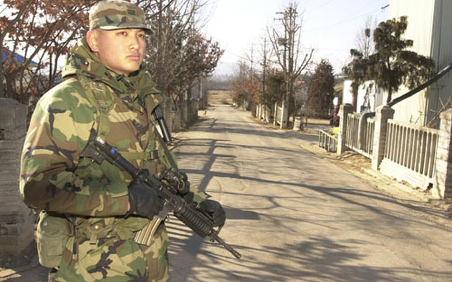 A Republic of Korea (ROK) Army soldier stands guard along one of the streets of Tae Sung Freedom Village. The street leads towards North Korea. Soldiers from the joint US /ROK Battalion provide security for the 226 residents of the village 24 hours a day.