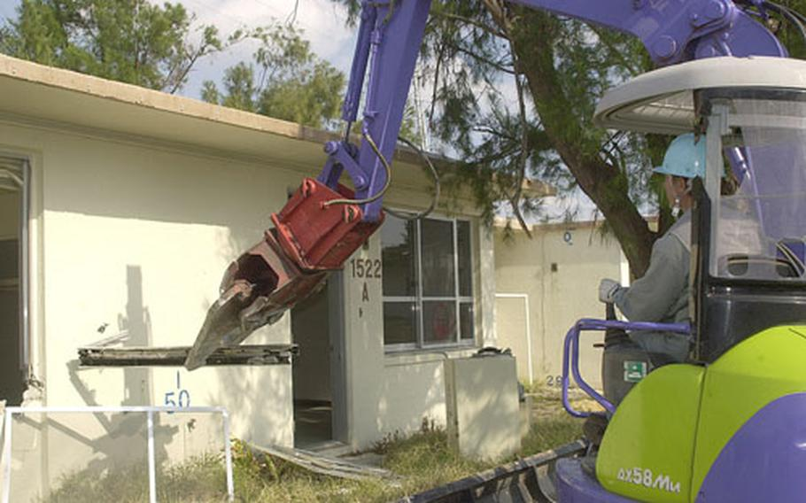 A heavy equipment operator uses a mechanical claw to rip off parts from a single-family home at Sada Family Housing Area. Demolition crews have begun knocking down hundreds of older homes in the housing area to make way for two high-rise towers totalling 136 units and 194 single- or two-story houses.