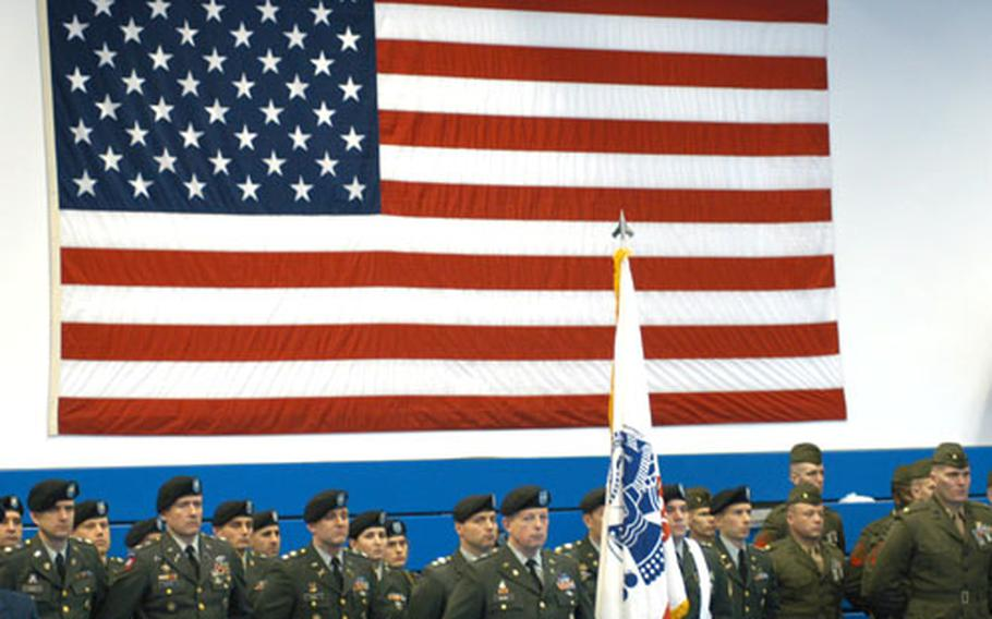 Soldiers of the United States European Command stand in front of a giant American flag at the EUCOM change of command ceremony in Stuttgart.