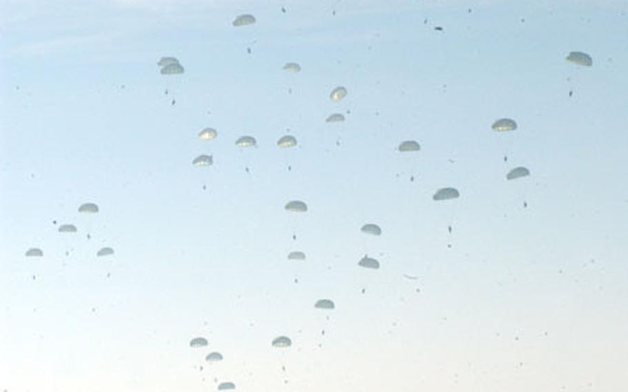 A soldier watches as 170 Airborne soldiers from 2nd of the 503rd Airborne Regiment descend near Klina, Kosovo, on Jan 15.