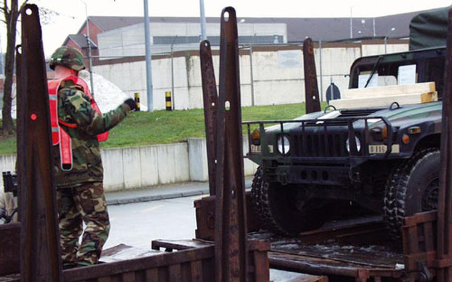 A 17th Signal Battalion soldier guides a Humvee aboard a troop transport train at the Harvey Barracks railhead in Kitzingen, Germany. The unit is one of several called up last weekend for deployment to an unknown destination in the Middle East.