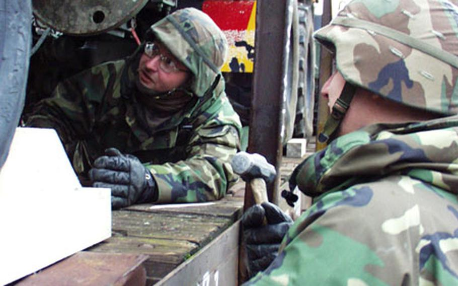Spc. Timothy Collins, left, and Spc. Jason Horn secure an Army truck to a transport train at Harvey Barracks in Kitzingen, Germany, in preparation for a deployment. The soldiers are members of the Kitzingen-based 17th Signal Battalion, one of several V Corps units called up last weekend for deployment to an unknown destination in the Middle East. This is the battalion's first call-up for possible combat duty since World War II, said battalion commander Lt. Col. Brian Moore.