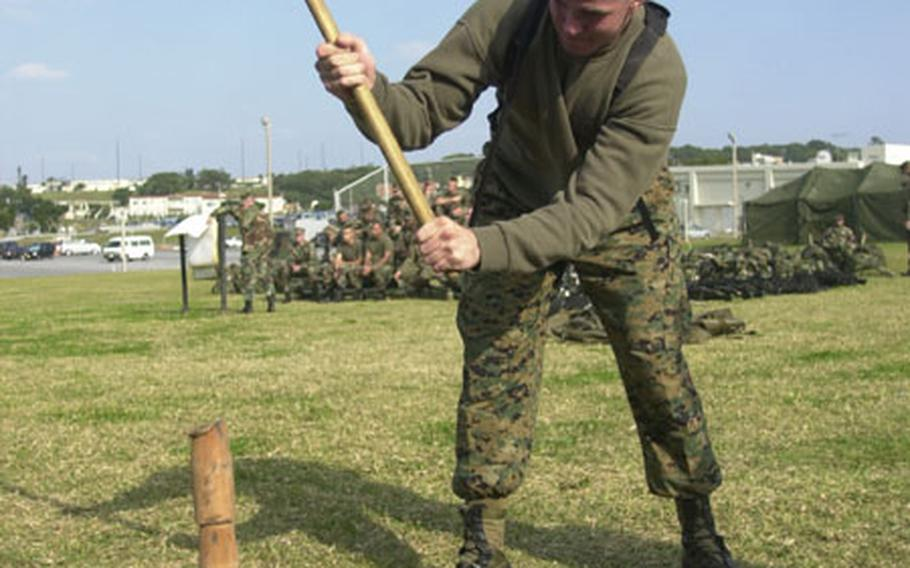 """Marine Sgt. Brian Hatfield drives tent stakes into the ground with a sledgehammer during a """"shakedown"""" period for a Marine support unit on Okinawa."""
