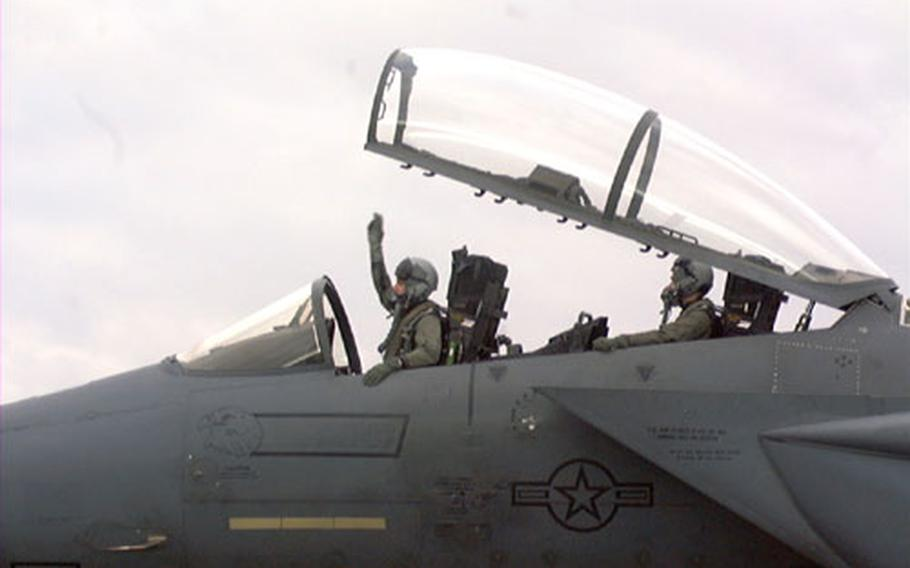 Lt. Col. Jay Silveria, commander of the 492nd Fighter Squadron at RAF Lakenheath, England, signals for his squadron's jets to fire up the engines Friday to begin a deployment to Portugal. Behind him is Capt. Mike Dunyak, the weapons system operator.