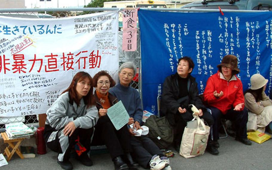 Anti-war protesters are staging a nine-day sit-in in front of the U.S. Consulate in Urasoe (pictured in background).