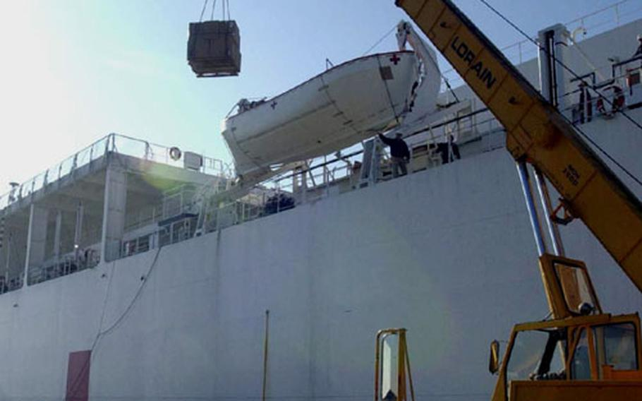 A crane is used to load supplies onto the U.S. Navy hospital ship USNS Comfort. The ship stopped in Rota this weekend to get supplies before heading to the Middle East.