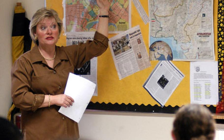 Standing in front of a pin-board with a map of Baghdad and Afghanistan and newspaper and magazine clippings of the Middle East, Heidelberg Middle School teacher Sylvia Rausch discusses current events with her seventh-grade pupils.