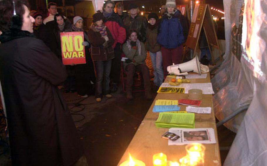 Demonstrators gathered outside Campbell Barracks in Heidelberg, Germany, on Thursday night, watch a video showing two active-duty U.S. soldiers speaking out against potential war in Iraq. Organized by the Stop the War Brigade, the 24-hour vigil outside Campbell was followed by a demonstration on Saturday.