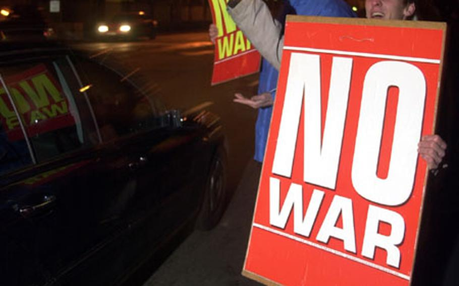 """Holding signs saying """"No War,"""" demonstrators gather outside Campbell Barracks in Heidelberg, Germany, on Thursday night to protest against potential war in Iraq."""