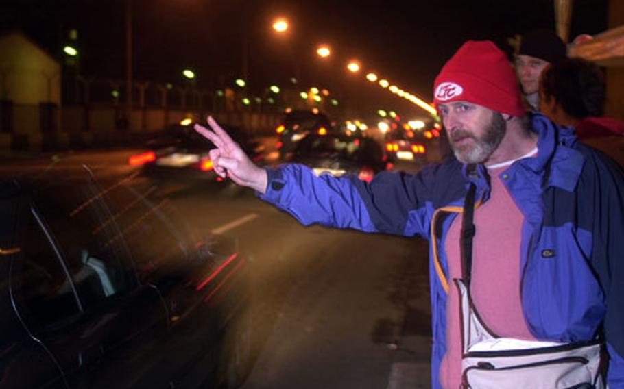 Tony Quantrell from Liverpool, England, flashes a peace sign at passing motorists outside Campbell Barracks in Heidelberg, Germany, on Thursday night. Quantrell, a member of the Scottish Socialist Party, flew in from the U.K. on Tuesday to take part in a protest against potential war in Iraq.