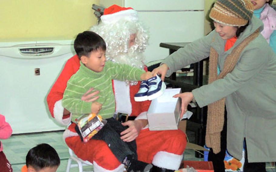 1st Lt. Ben Bartlett, an F-16 pilot, plays Santa Claus on Christmas Day at the Kae Chong Orphangage near Kunsan Air Base. Airmen donated about $10,000 during the holidays to help area orphanages.