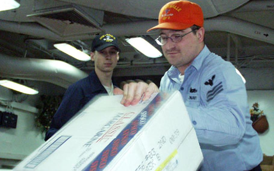 """Petty Officer 1st Class Regan Schraeder moves frozen food into the freezer on the USS La Salle. Schraeder said he got """"slammed"""" — involuntarily assigned — when he asked the Navy to keep him overseas, but he was sent to recruiting duty in the States."""