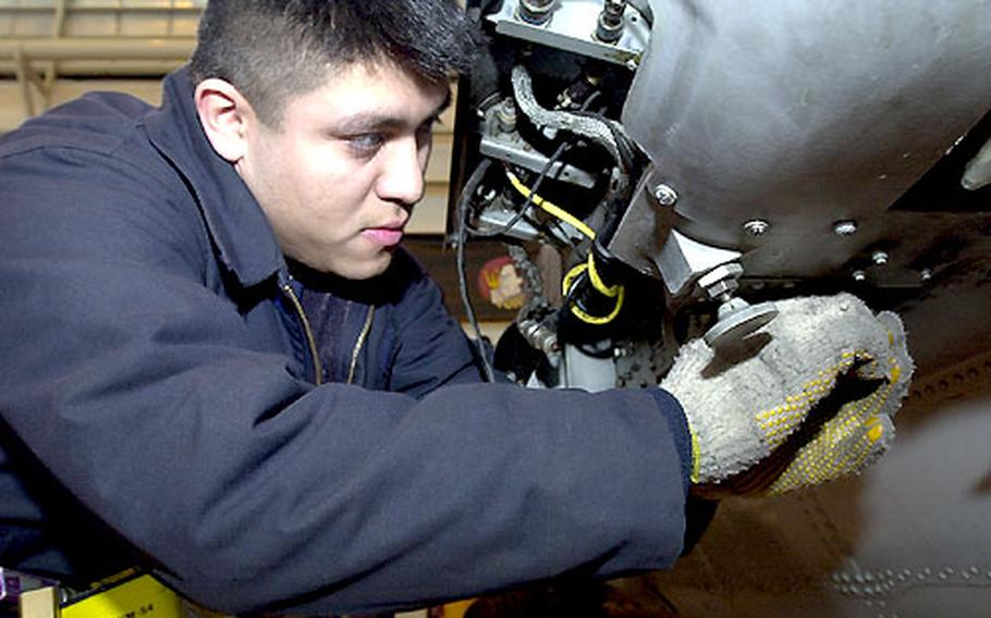 Petty Officer 2nd Class Ronnie Cubias adjusts an assembly that will hold a torpedo on a SH-60B helicopter.