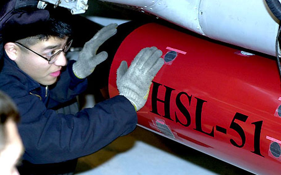 Petty Officer 2nd Class Ronnie Cubias checks to make sure a torpedo is properly installed aboard a SH-60B helicopter.