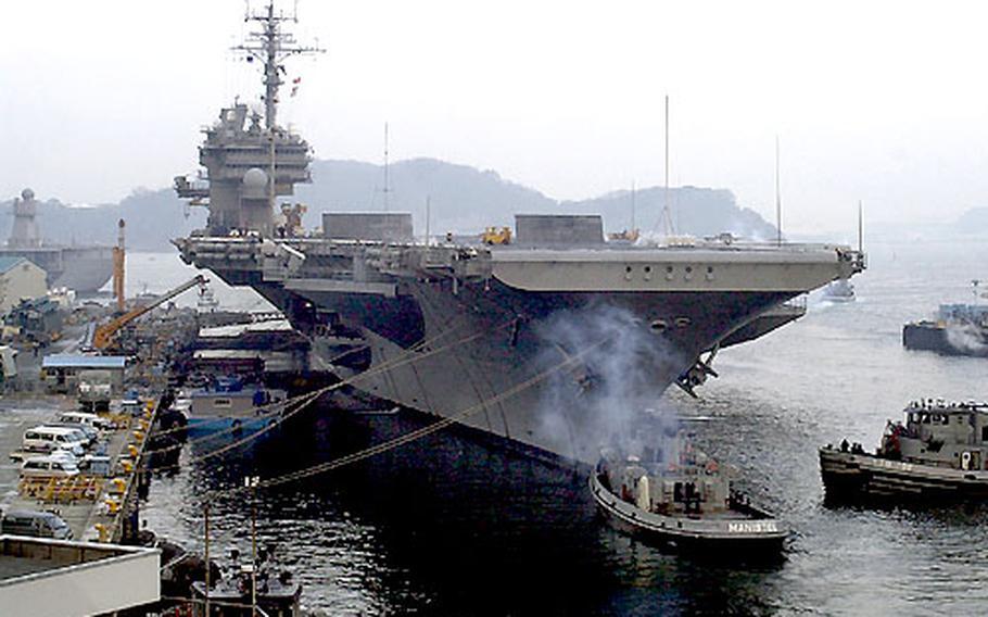 Tug boats prepare to guide the USS Kitty Hawk out of port Monday morning at Yokosuka Naval Base, Japan.
