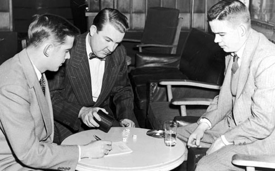 Bill Mauldin, right, plays a parlor game with other journalist at the Tokyo Correspondents' Club in 1952.