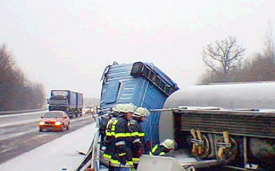 Emergency workers examine an overturned truck on autobahn A3 following a traffic accident on the snowy morning of Jan. 13. Before the accident, an Army Humvee had slowed as it encountered a traffic jam. The Humvee skidded and jackknifed. About 45 minutes later, the German tanker truck carrying diesel fuel hit the Army trailer and overturned.