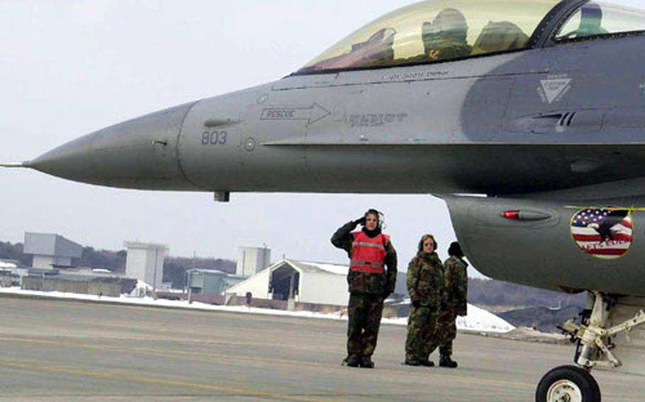 Senior Airman Sean Rafferty, an F-16 crew chief, salutes a Misawa F-16 pilot at the conclusion of the end of runway inspection at Misawa Air Base, Japan.