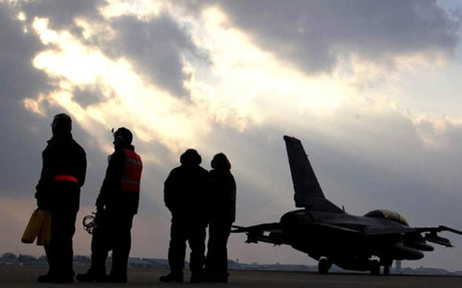 Their vital jobs completed, crew chiefs and weapons loaders watch as a Misawa F-16 leaves for a mission at Misawa Air Base, Japan.