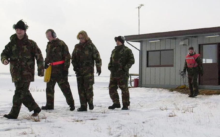 Crew chiefs Senior Amn. Rob Hunt, Amn. Aaron Marwick, weapons loader Senior Amn. Laura Quiroz, and Airman 1st Class Sean Rafferty, another crew chief, walk across a snowy field to await departing fighter aircraft at Misawa Air Base, Japan.