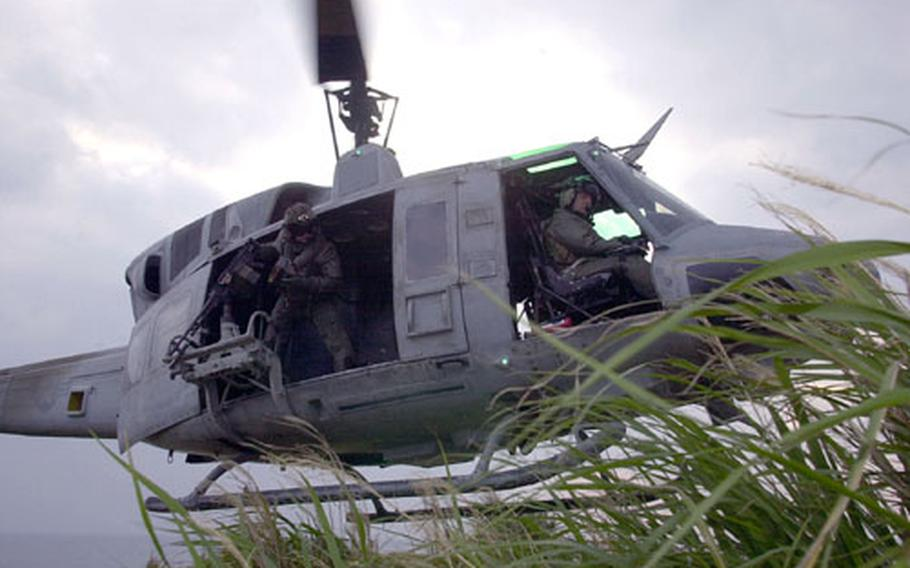 Pilots and crews of a UH-1N Huey lift off after inserting an infantry team off the coast of Okinawa. Marines from Marine Light Attack Squadron 367 practiced dropping off and picking up infantry while under fire.
