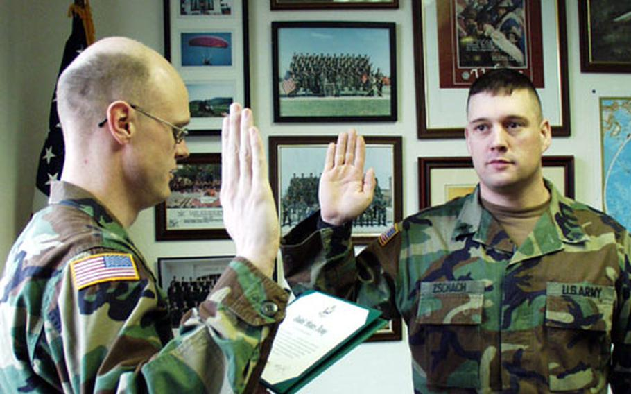 """Sgt. Dean Zschach (right) of the 1st Infantry Division's headquarters company is re-enlisted by Capt. Robbin Halstead at Leighton Barracks in Würzburg, Germany. Zschach, 32, had to re-enlist for three years instead of two because of new """"retention moderation"""" policies designed to combat recent overmanning in the Army."""