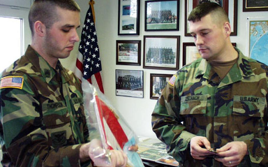 Sgt. Dean Zschach (right) of the 1st Infantry Division's headquarters company receives a unit flag and a coin as re-enlistment gifts from Staff Sgt. Mark Thompson, a 1st ID re-enlistment counselor.