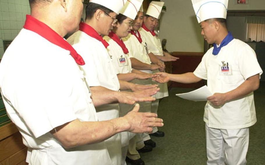 Cooks in the Camp Jackson Dining Facility have their hands inspected for cleanliness by Kim Do Pung prior to the lunch meal on Thursday.