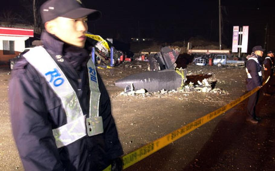 Korean National Police form a cordon around the crash site of an Osan-based U-2 Dragonlady reconnaissance aircraft. Part of a section that holds reconnaissance sensors and the sections of the aircraft's tail are visible on the gound between the policeman. The U-2 reportedly crashed during a training mission from Osan.