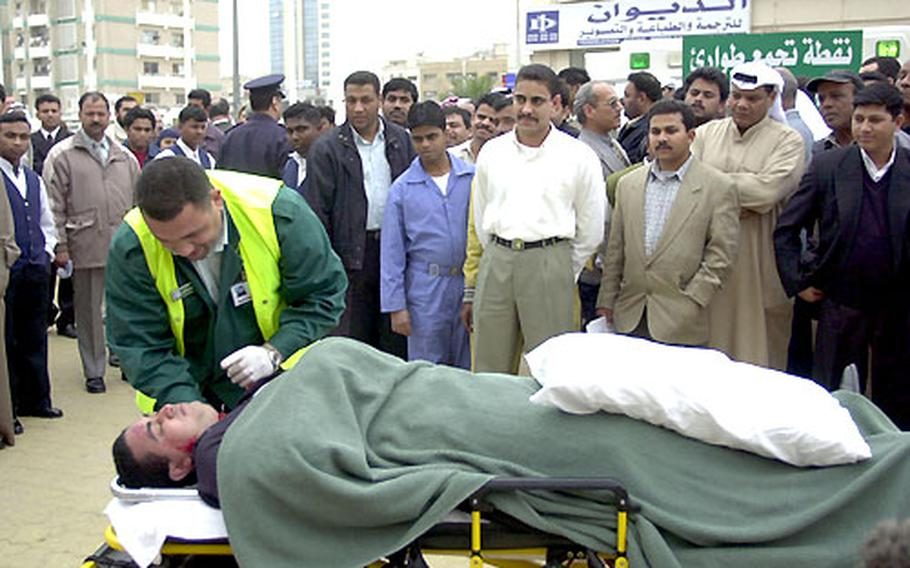 """Bystanders watch as emergency medical personnel treat a """"victim"""" during a bomb attack drill in Kuwait City on Tuesday."""