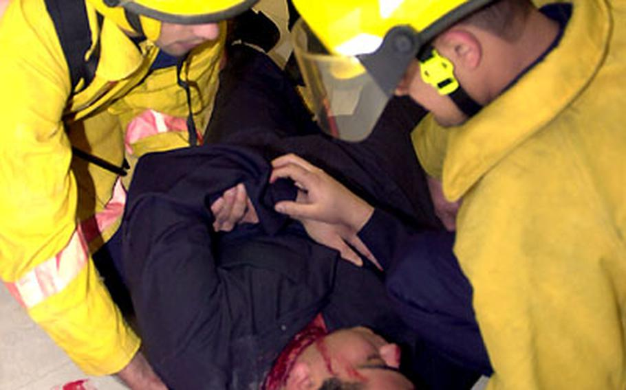 """Emergency workers tend to a """"victim"""" during a bomb attack drill Tuesday in Kuwait City."""