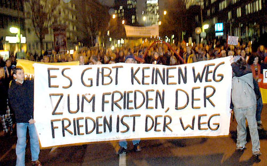 """Carrying a banner reading, """"There is no way to peace, peace is the way,"""" anti-war protesters march in Frankfurt, Germany, on Monday."""