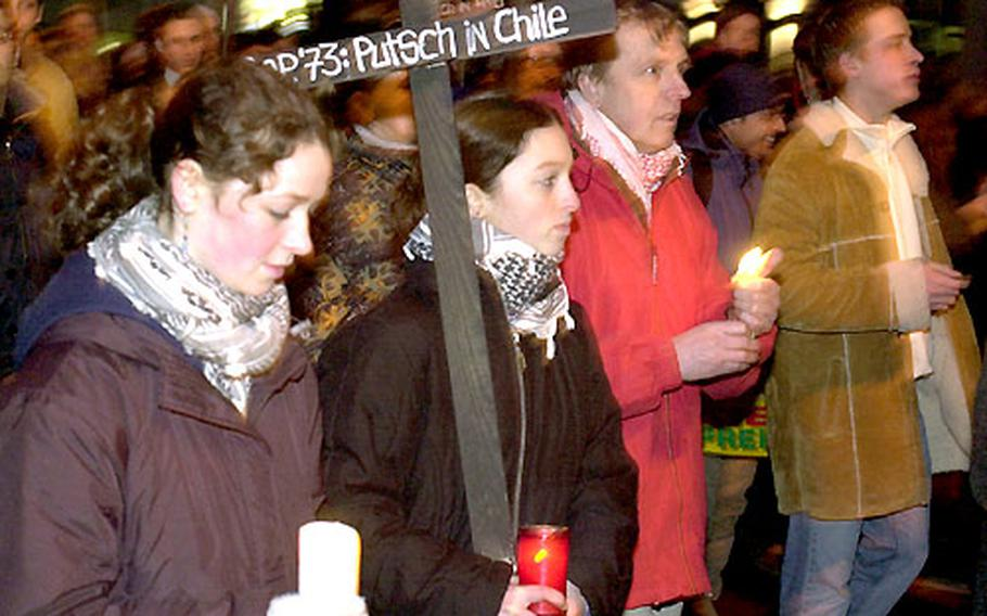 Carrying candles and crosses with what they consider to be past acts of American aggression written on them, anti-war protesters march in Frankfurt, Germany, on Monday.