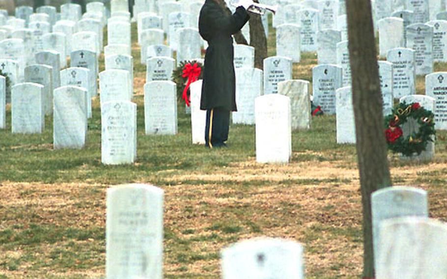 """Sgt. 1st Class Michael Yoder, a bugler for the U.S. Army Band, plays """"Taps"""" at Bill Mauldin's funeral."""