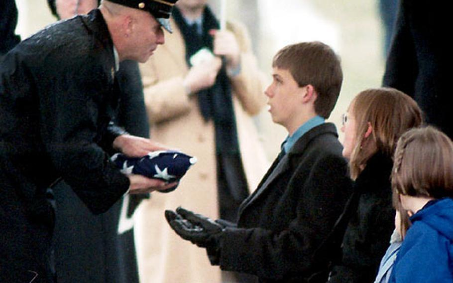 Sgt. Maj. of the Army Jack Tilley presents the flag to Bill Mauldin's 16-year-old son, Sam. At right is Mauldin's former wife, Christine Lund.