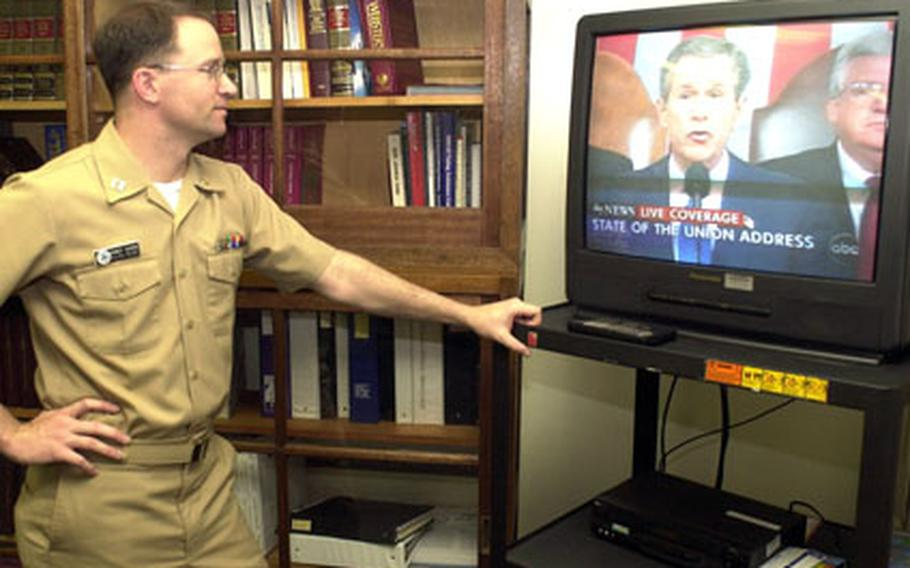 Lt. Randy Vavra, officer in charge of Sasebo Naval Base's Navy Legal Services Office, watches from his office as President George W. Bush deliver his 2003 State of the Union address Wednesday.