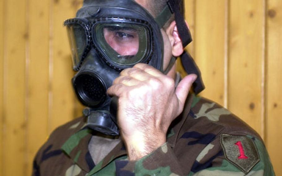 Sgt. Kirten Stoute, a nuclear, biological and chemical weapons expert with the 1st Infantry Division checks out a gas mask as the division headquarters and many of its support units prepare for deployment into Turkey.