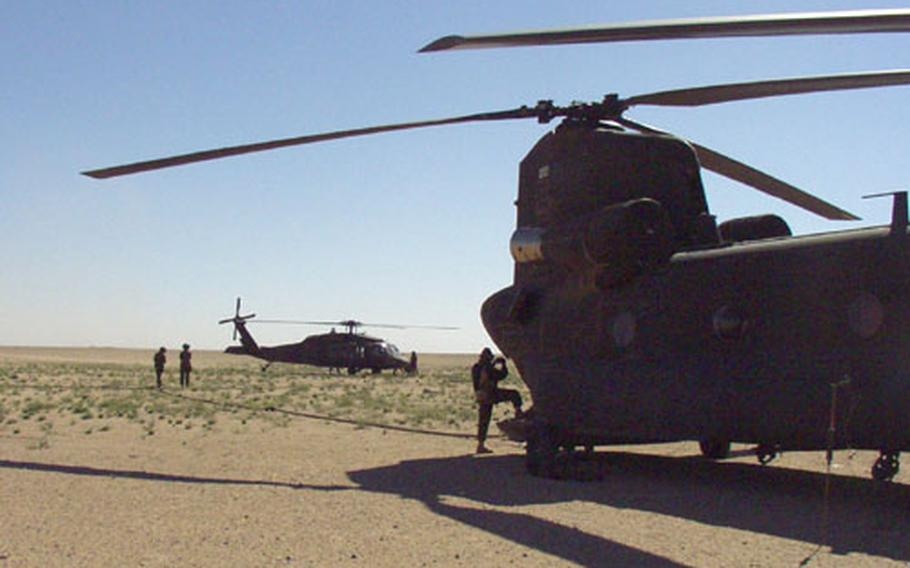 Crew members from a Black Hawk helicopter, left, hook up to a Chinook during a fat-cow refueling exercise in the Kuwaiti desert.
