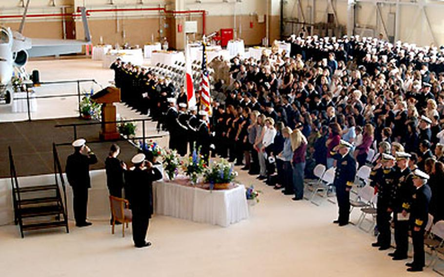 Servicemembers pay their respects to Lt. Nathan White during the memorial service inside the hangar of VFA-195 at NAF Atsugi.