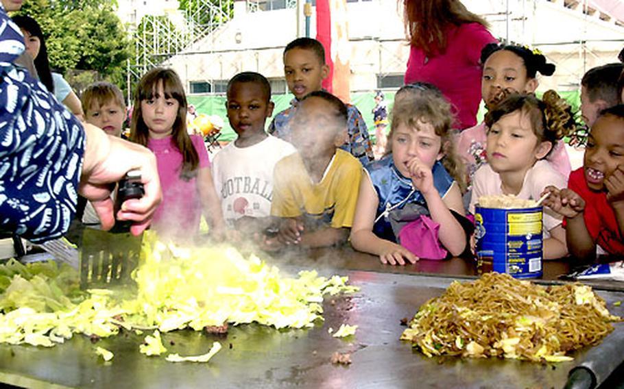 Children from Yokota West Elementary School learn about making yakisoba during the Nihon Matsuri Festival.