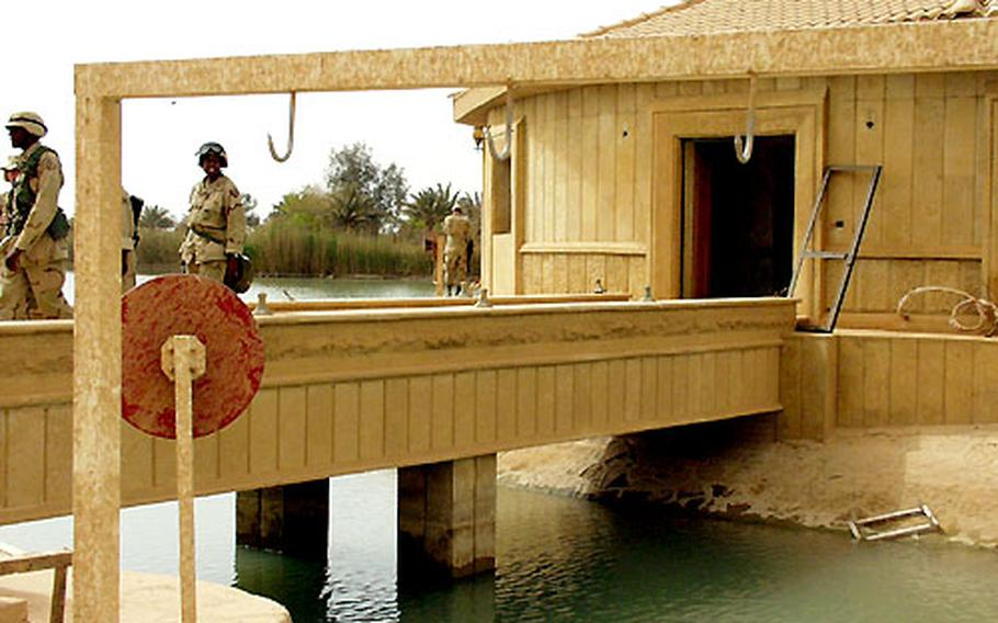 Large hooks to hang the fish stocked in the lakes on the palace compound abound everywhere on the complex. These hooks are near a dock that has been commandeered by troops who will use it as offices and living space.
