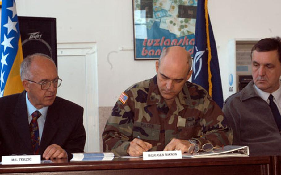 Mustafa Terzic, general manager of Tuzla International Airport, left, looks on as Brig. Gen. James Mason, commander of Multinational Brigade North, signs one of the documents which made the civilian airport reopening possible. The airport which was shut down after the Sept. 11 terrorist attacks for security reasons, and was reopened Wednesday in a ceremoney attended by SFOR, local government officials and airport staff.