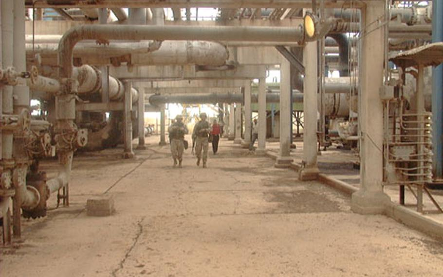 Surrounded by a symphony of hums and hisses, Maj. Robert Gowan (left) and 1st Lt. Brian Nash of the 173rd Airborne Brigade, Vicenza, Italy, walk through a corridor of pipes at the large oil facility north of Kirkuk in northern Iraq. Despite the infrastructure's shaky state, the facility is working, pumping 60,000 barrels of oil a day. At its peak, the facility's daily output was 280,000 barrels.