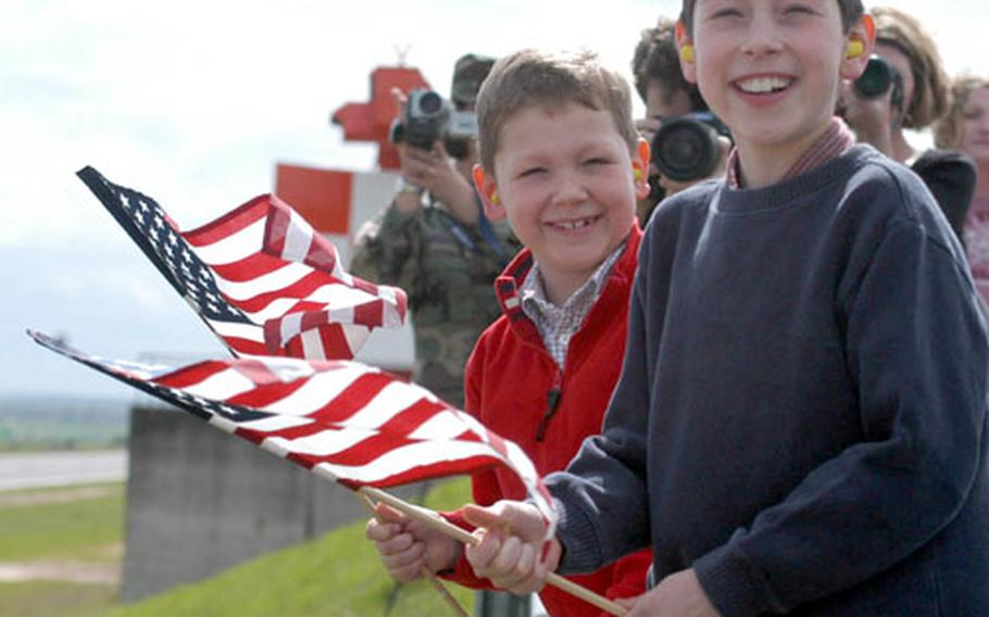 Alex, left, and Dalton wave American flags as they watch their dad Lt. Col. Hank Reed land his F-16CJ aircraft at Spangdahlem Air Base, Germany, Thursday. About 24 airplanes of the 52nd Fighter Wing's 22nd and 23rd Fighter Squadrons returned to this base in Germany's Eifel mountains from an undisclosed location after flying missions for Operation Iraqi Freedom. Reed is the commander of the 22nd Fighter Squadron.