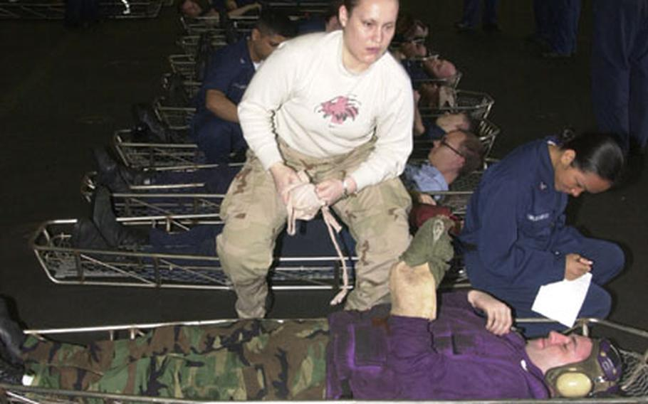 Medical staff from the USS Kitty Hawk treat a long row of simulated casualties in the main hangar bay. Without port calls, the trip home has been full of exercises and drills.