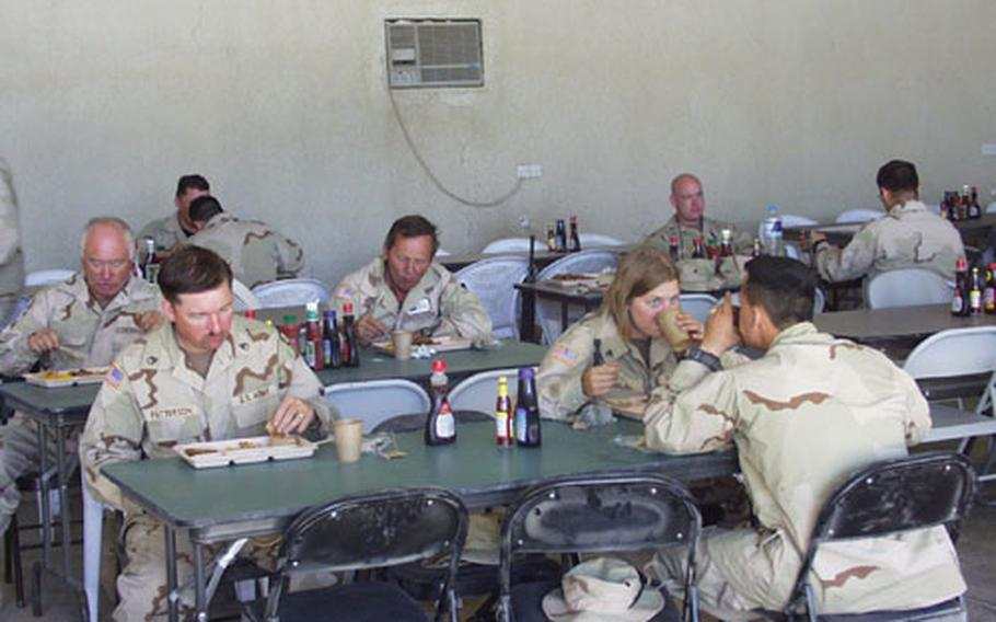 V Corps soldiers enjoy their first hot meal at Victory Camp outside Baghdad, Iraq, on Friday. Hot meals are tentatively planned for twice a week.
