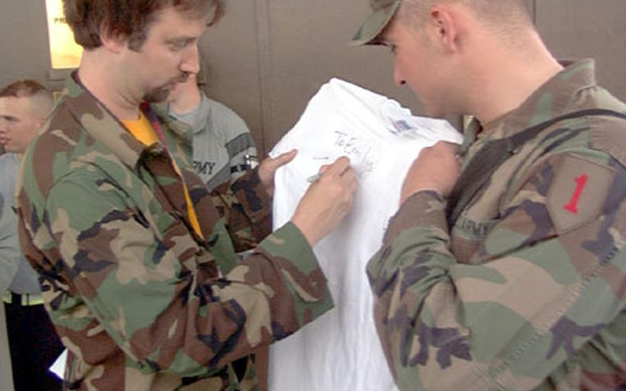 Comedian Tom Green signs an autograph for a 1st Infantry Division soldier at Camp Bondsteel, Kosovo, on Friday. Geen, known for his antics on his own MTV show, is on a weeklong tour of the Balkans through the United Service Organizations.
