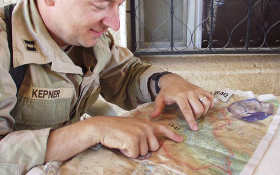 Army Capt. Mike Kepner, commander for V Corps headquarters and headquarters company, shows on a map the route he and his staff took as they kept supplied and moved the forward headquarters element of V Corp in the fighting across Iraq.