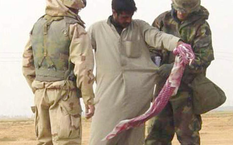 A soldier from the 527th Military Police Company, from Giessen, Germany, conducts a body search on an Iraqi citizen during a random checkpoint in southern Iraq as a translator watches.